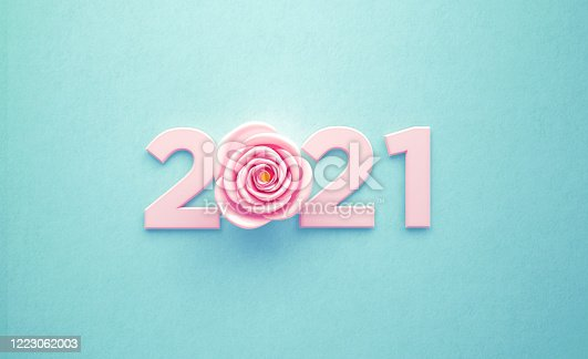 Pink rose and number forming 2021 over turquoise background. Horizontal composition with copy space. New year concept.