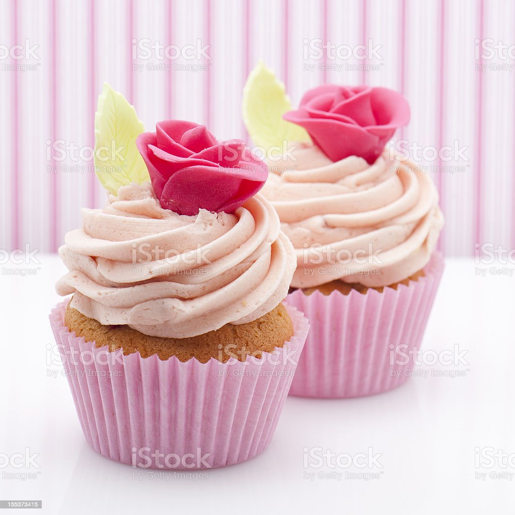 Pink rose cupcakes on pink striped background royalty-free stock photo