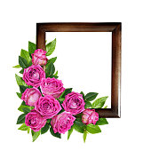 istock Pink rose flowers and green leaves in a corner floral arrangement on wooden frame 1017165676