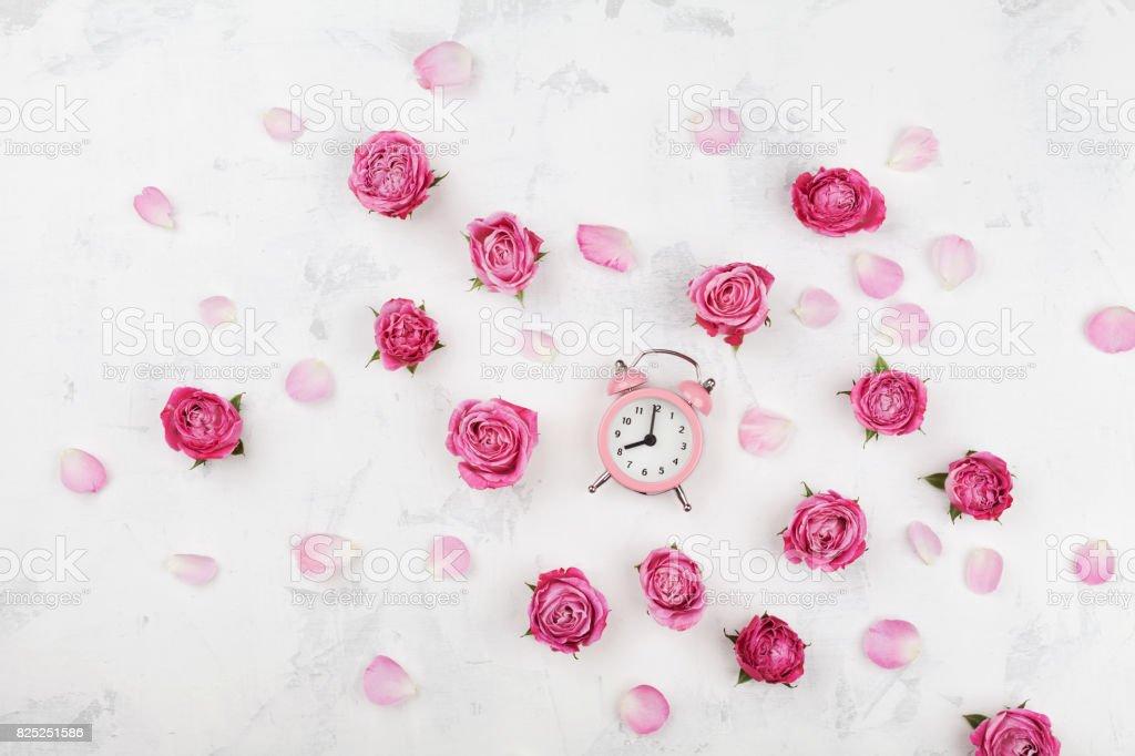 Fleurs roses roses pétales et réveil sur bureau blanc poser de