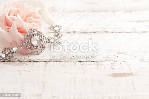 A pink rose and silver jewellery on white wood boards.