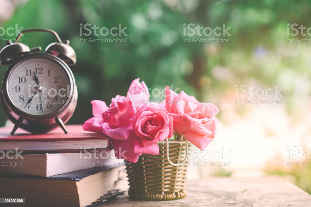 pink roses bouquet ,clock and book on wooden table over nature green...