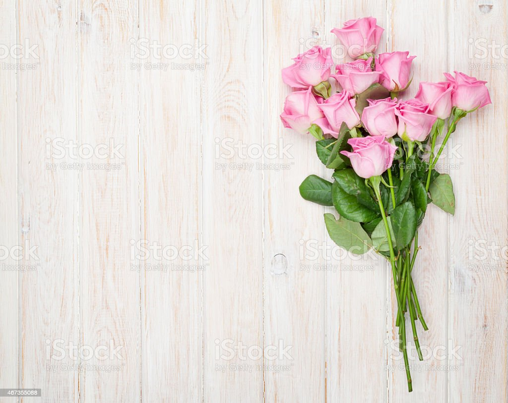 Pink roses bouquet over wooden table stock photo