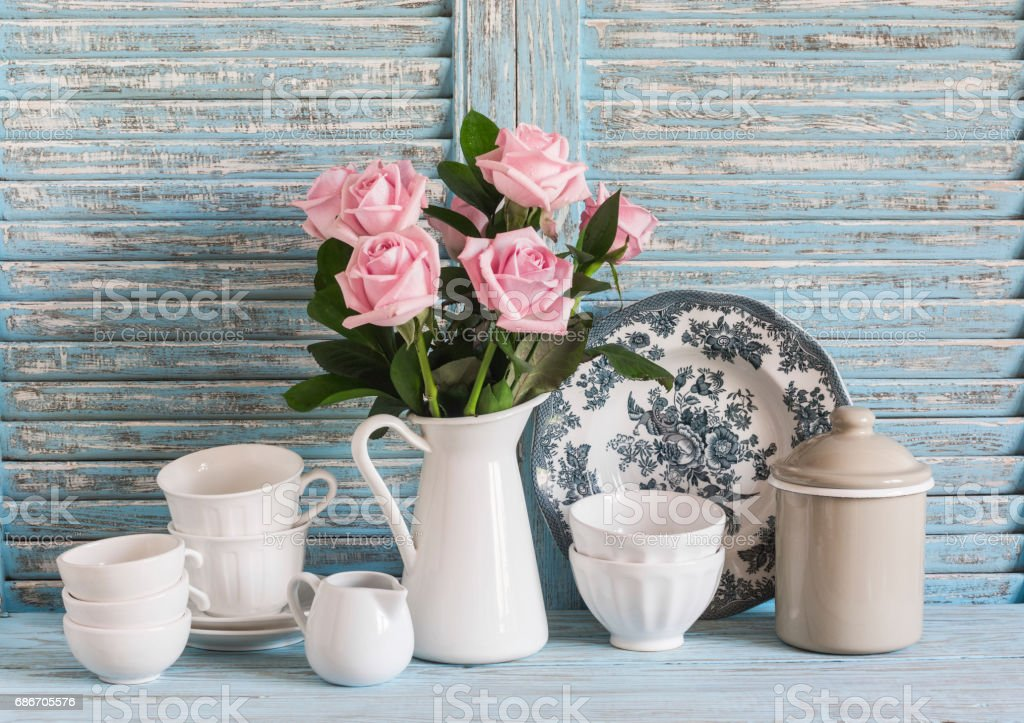Pink roses in a white enameled pitcher, vintage crockery on blue wooden rustic background. Kitchen still life in vintage style. Flat lay stock photo