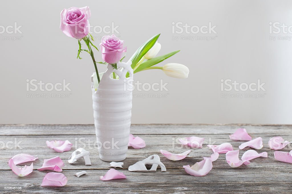 pink roses in broken vase on old wooden table stock photo