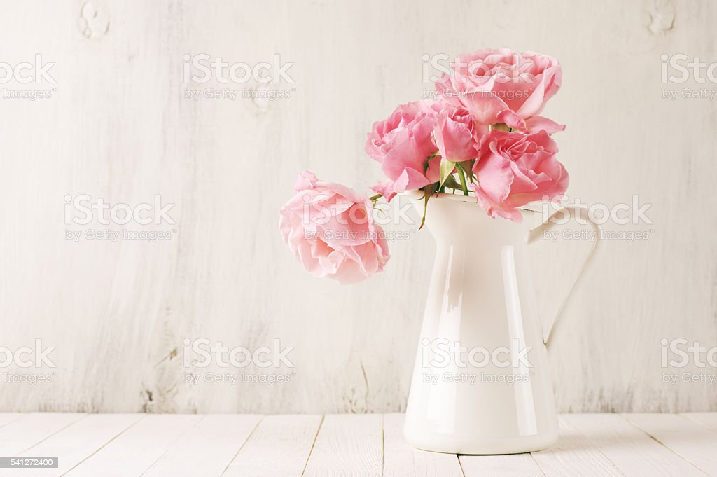 Pink roses in jug stock photo
