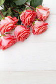 istock Pink roses on white wooden background. Floral frame, Mothers day, st. Valentines day roses, Bouquet of pink roses, Floral background image with copy space for text 1193507393