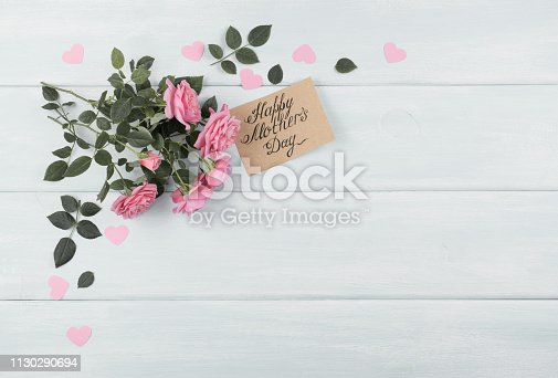 Pink roses with paper greeting card for Mothers day on background of shabby wooden planks. Copy space. Top view. Flat design.