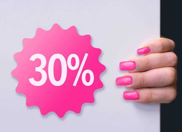 Pink rosette with 30% discount and matching acrylic nails Woman holding a white board with  discount  rosette and matching acrylic nails pink nail polish stock pictures, royalty-free photos & images