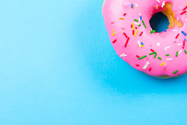 Pink round donut on blue background. Flat lay, top view. stock photo