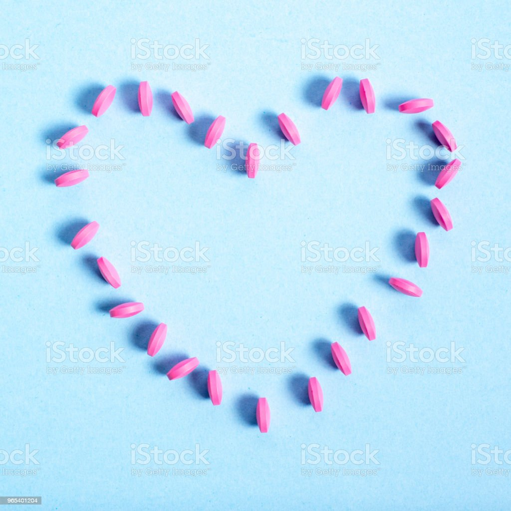 Pink round tablets spread out in the shape of  heart royalty-free stock photo