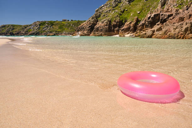pink rubber ring at the shoreline at pedn vounder beach, views towards porthcurno. - rubber ring stock pictures, royalty-free photos & images