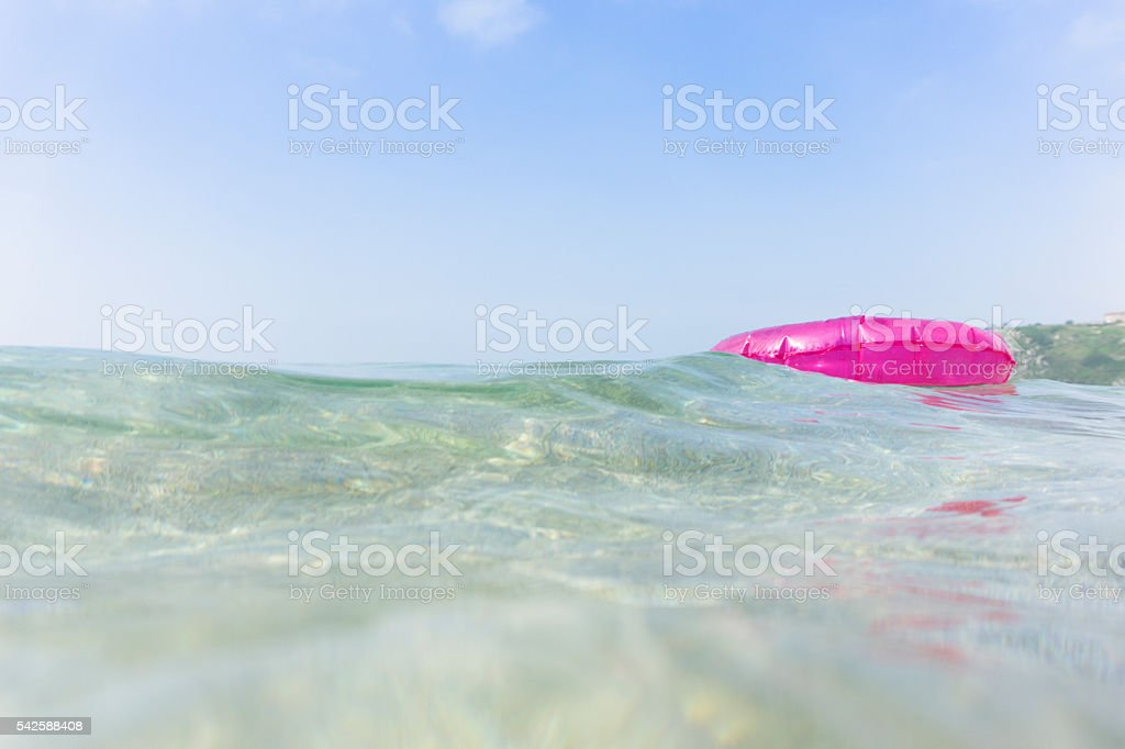 Pink rubber ring floating in the sea, South Cornwall. stock photo