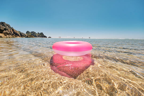 pink rubber ring floating on the clear shallow idyllic sea at pedn vounder beach, cornwall on a perfect june day. - rubber ring stock pictures, royalty-free photos & images