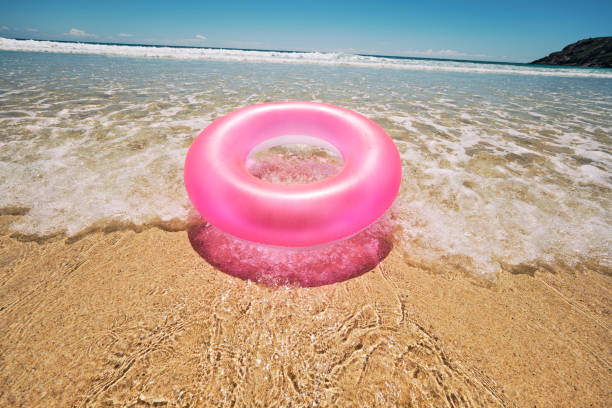 pink rubber ring floating on the shallow clear idyllic sea at the shoreline of pedn vounder beach, cornwall on a hot sunny june day. - rubber ring stock pictures, royalty-free photos & images