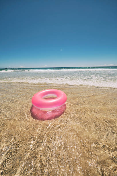 pink rubber ring floating on the shallow clear idyllic sea at the shoreline of pedn vounder beach, cornwall on a hot sunny june day. - rubber ring stock photos and pictures