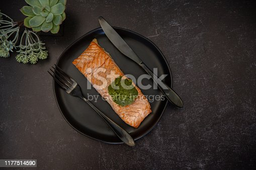 pink salmon fillet roasted grilled on a black plate with a scoop of pesto