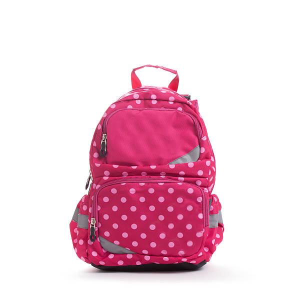 Pink school backpack with white dots isolated on white stock photo