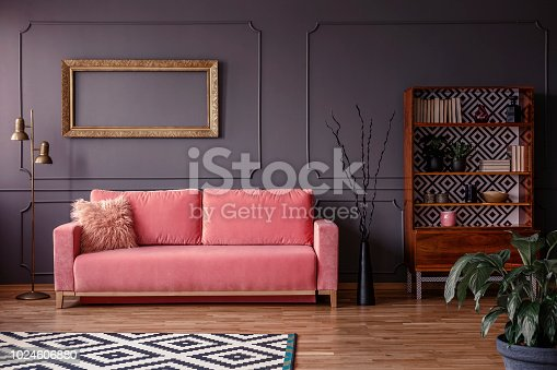 Pink settee against grey wall with mockup of gold frame in elegant living room interior. Real photo