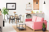 Pink settee near black chairs at dining table in flat interior with kitchenette and poster. Real photo