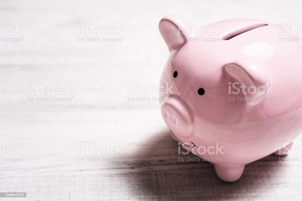 Ein Rosa Sparschwein auf einem Tisch lächelnd – Foto