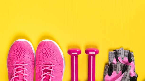 rosa turnschuhe, handschuhe und hanteln liegen in einer reihe auf einem gelben hintergrund, ein ort für eine inschrift - rosa training stock-fotos und bilder