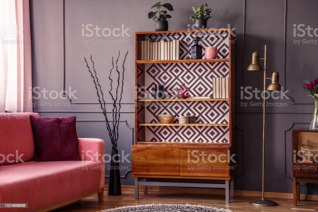 Houten Woonkamer Kast.Roze Sofa Naast Houten Kast En Gouden Lamp In Grijs Woonkamer