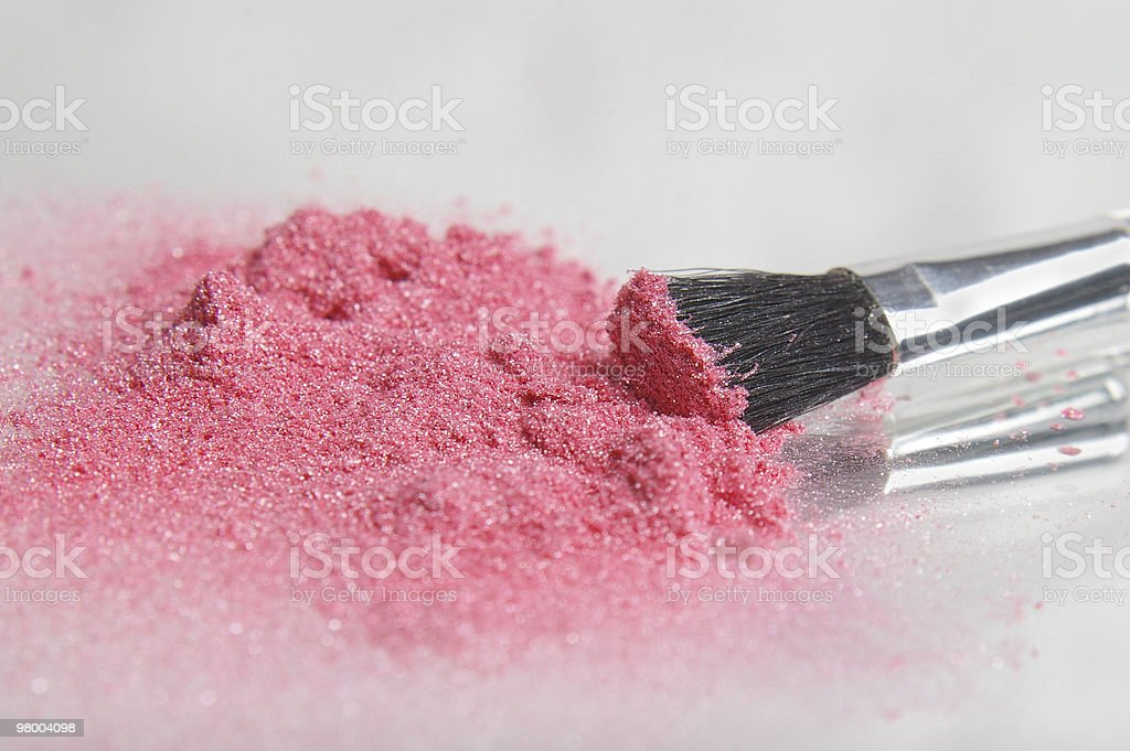 Pink sparkle makeup in a pile with a brush stock photo