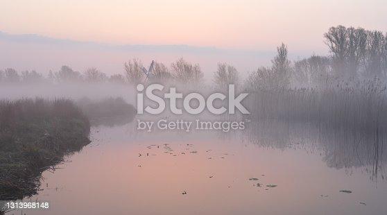 Foggy dawn over a creek in the Dutch countryside near a windmill.