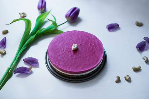 Pink Spring Raspberry Cake with cashew nuts on white table and purple tulips.