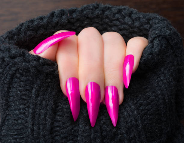 Pink stiletto shaped nails in warm cardigan Woman showing her pink stiletto shaped nails in warm cardigan pink nail polish stock pictures, royalty-free photos & images