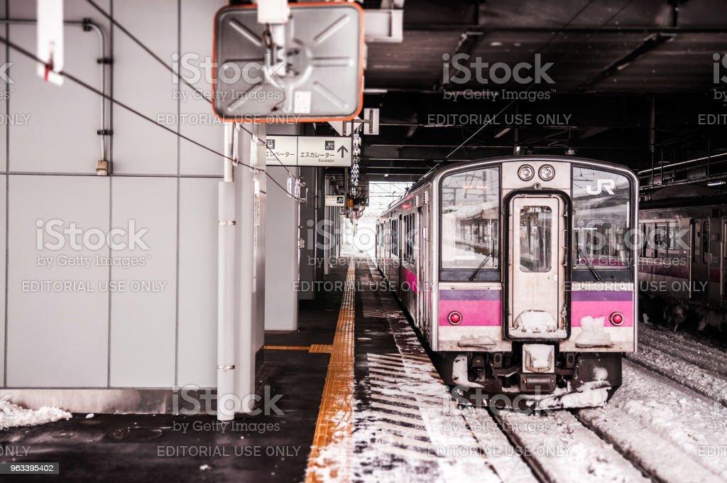 Pink strip JR East 701 Series commutor train at Hirosaki Station in winter, EMU train opperated on Ou Main Line between Akita and Aomori - Zbiór zdjęć royalty-free (Dworzec)