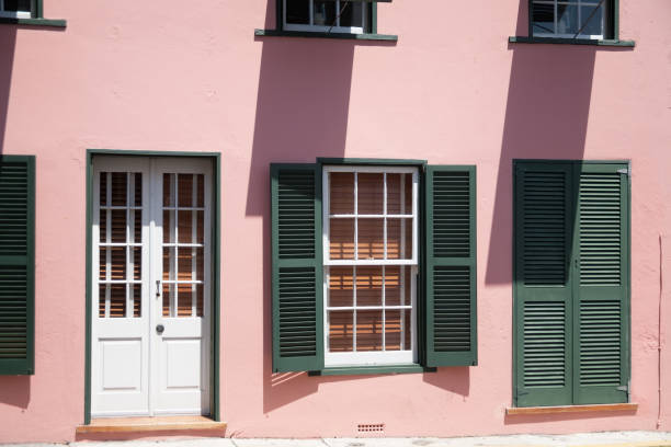 Pink Stucco building with green shutters in St. Georges stock photo