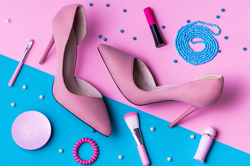 Pink Suede High Heels on pink and blue split background with accessories.