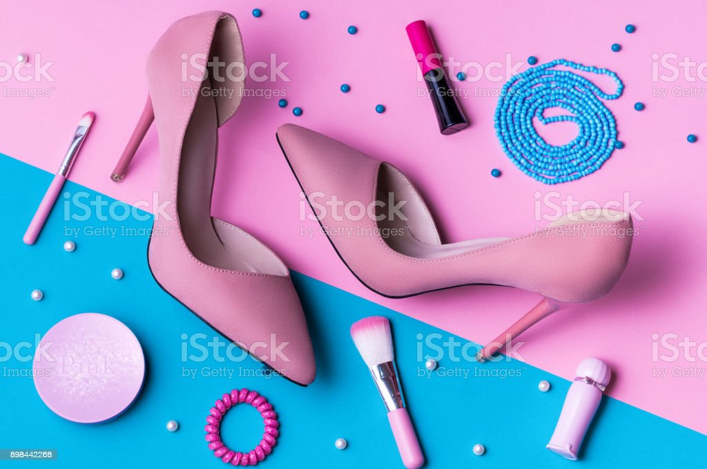 Pink Suede High Heels on pink and blue split background with accessories. stock photo