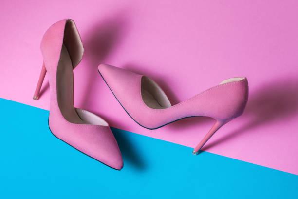 roze suede hoge hakken op roze achtergrond - hoge hakken stockfoto's en -beelden