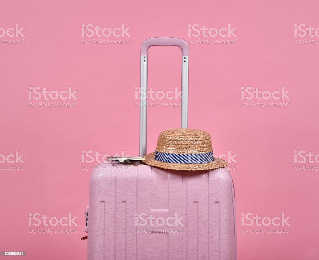 Rosa Koffer und Pass über rosa Hintergrund, Reise dokumentieren und Reise-Konzept. – Foto