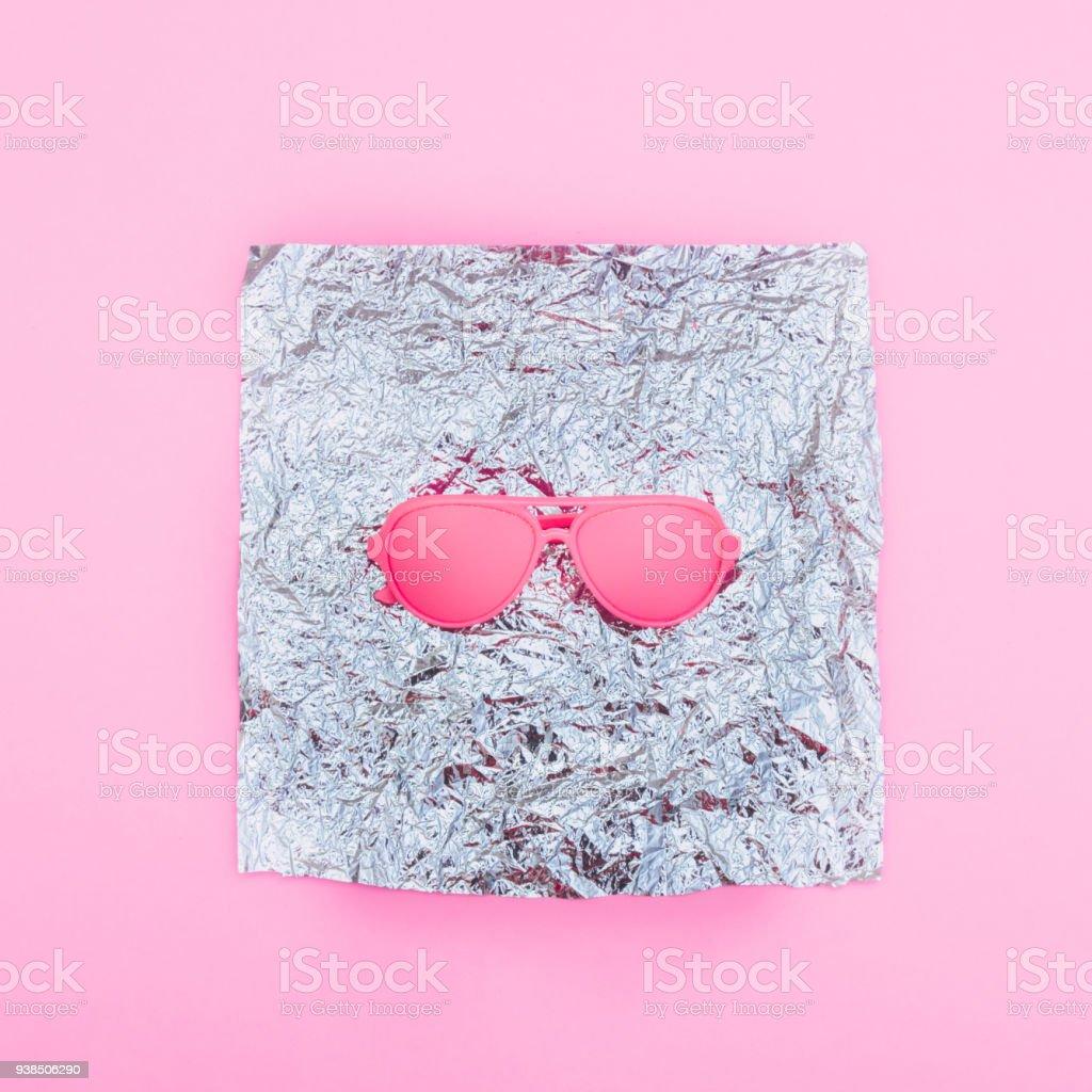 pink sunglasses on holographic metallic silver foil. fashion creative...