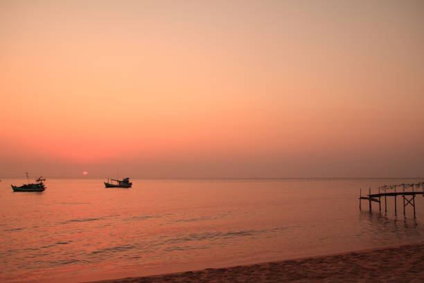 pink sunset at the beach with boat and pier - italiansight foto e immagini stock