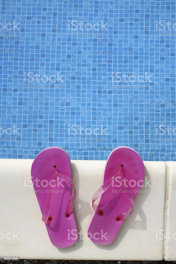 Rosa Swimmingpool Sandalen auf einem blauen Wasser Hintergrund – Foto