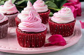 Close up of pink and white swirled buttercream frosting on a red velvet cupcake. Cupcakes are on a decorative pink plate. Fresh pink rose petals adorn the table and fresh pink roses are seen in the background.