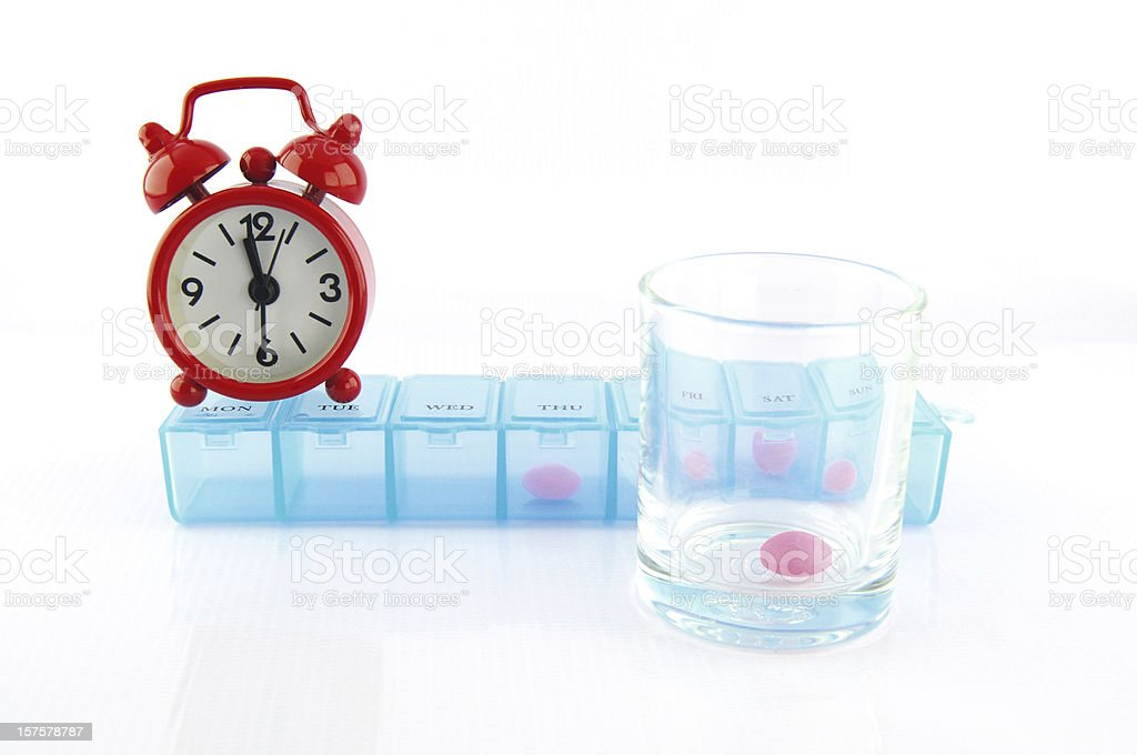 Pink tablet and redclok in daily pill box royalty-free stock photo