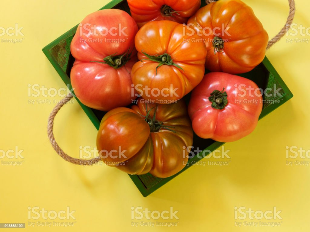 Pink tomatoes in wooden case stock photo