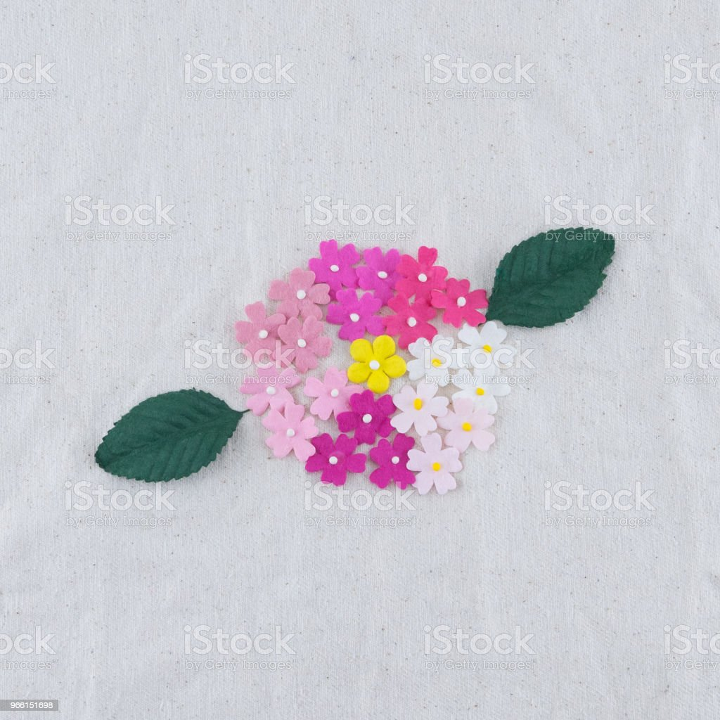 Pink tone paper flowers and green leaves bouquet on muslin fabric - Стоковые фото Букет роялти-фри