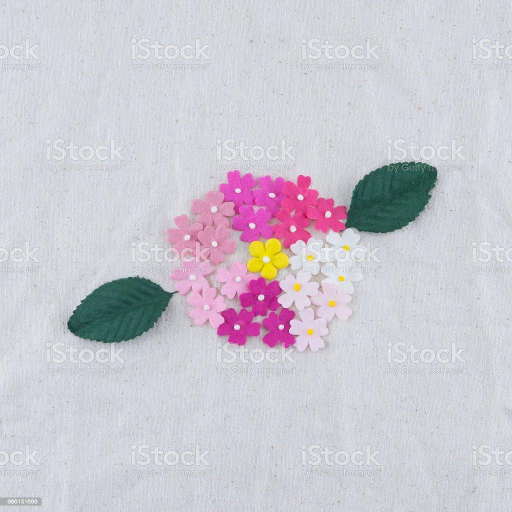 Fiori di carta tono rosa e bouquet di foglie verdi su tessuto mussola - Foto stock royalty-free di Amore