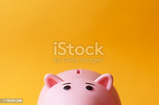pink toy piggy money box on yellow backgroung with copy space