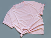 istock Pink t-shirt mock up flat lay on grey background 1258133095
