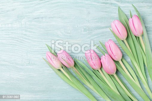 659293084istockphoto Pink tulip flowers on rustic table for March 8, International Womans or Mothers day. Beautiful spring card. 912061392