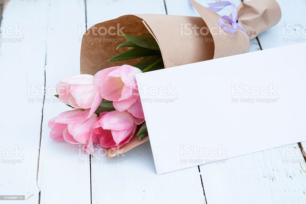 Pink tulips next to a white envelope stock photo