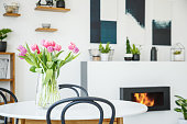Pink tulips on dining table in white room interior with plants and poster above fireplace. Real photo